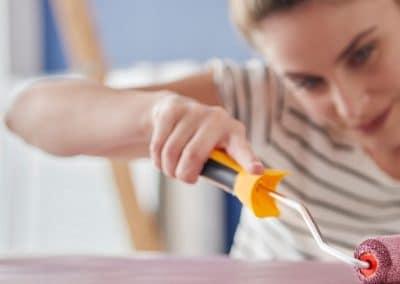 Mujer pintando un mueble con un rodillo