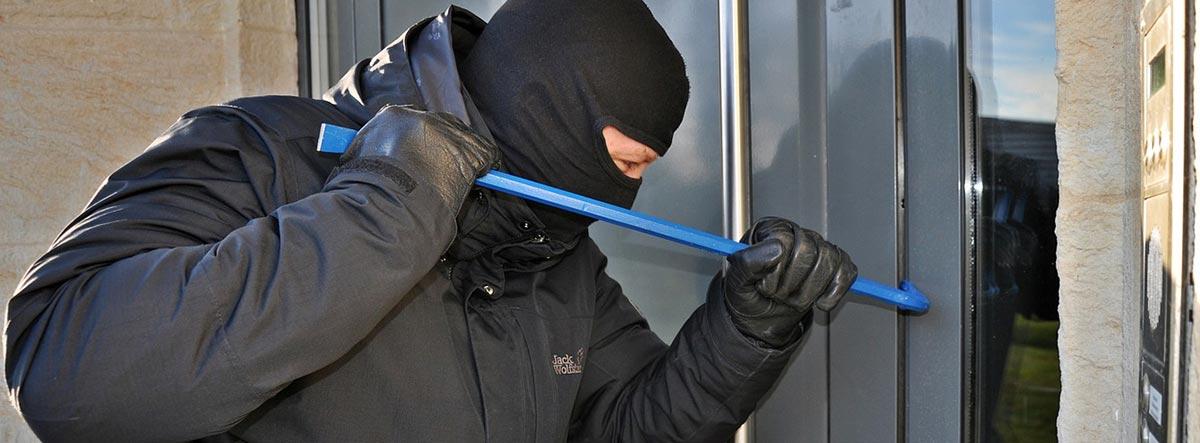 Ladrón forzando una puerta con una palanca