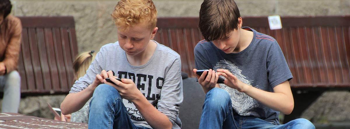 Dos niños de la generación táctil usando teléfonos móviles