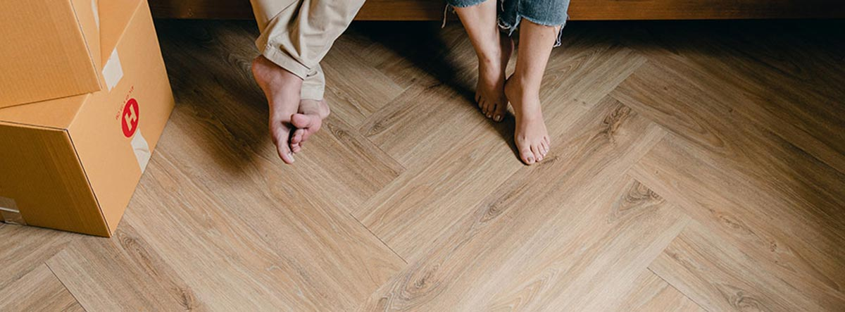 Una pareja descalza en el suelo radiante de su casa