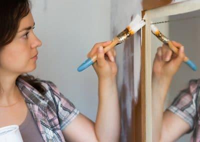 Mujer con una paletina pintando un armario de blanco
