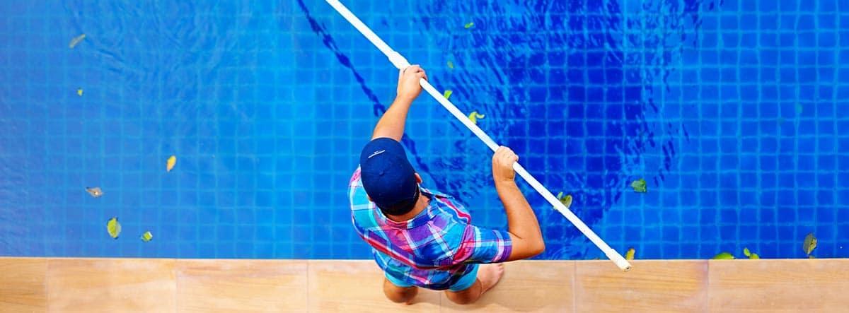 Hombre limpiando una piscina de hojas