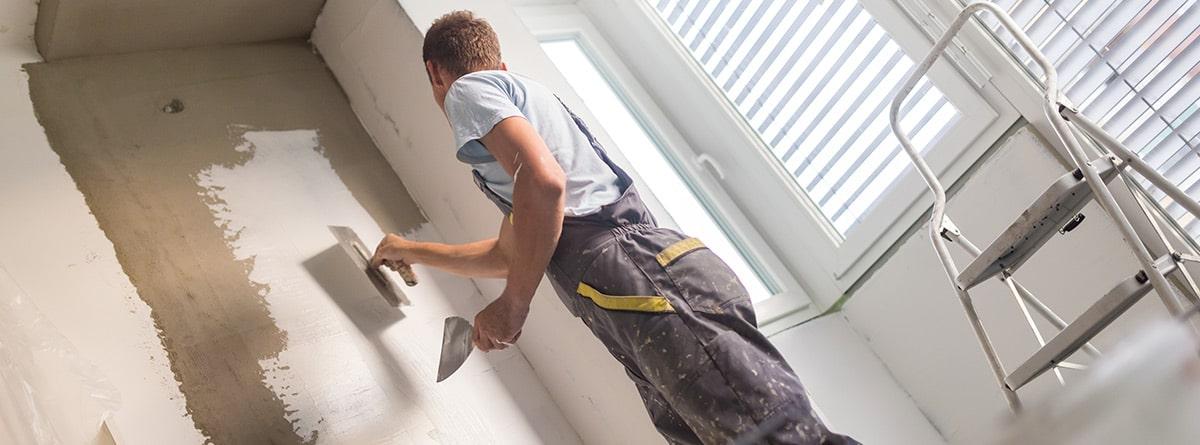 Hombre reparando fisuras en las paredes de una casa