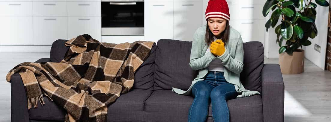 Mujer abrigada y con gesto de frío sentada en el sofá de una casa