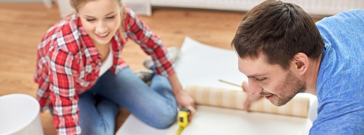 Hombre y mujer midiendo papel pintado