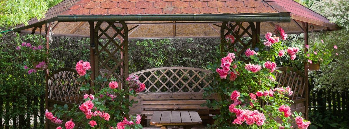 cenador de madera exento rodeado de plantas