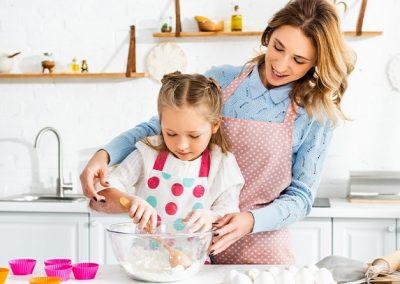 Mujer y niña preparando una receta de repostería