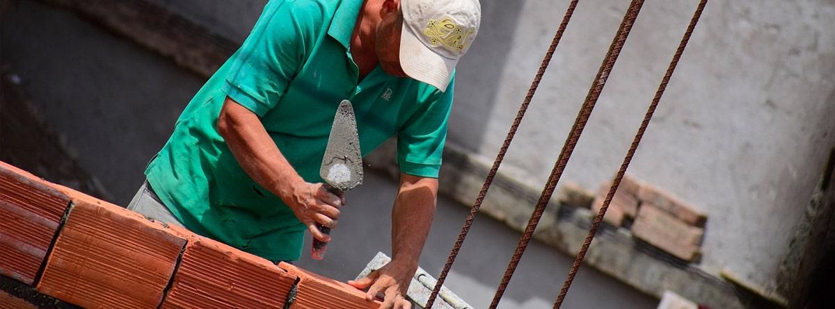 Hombre con mono verde colocando ladrillos con cemento