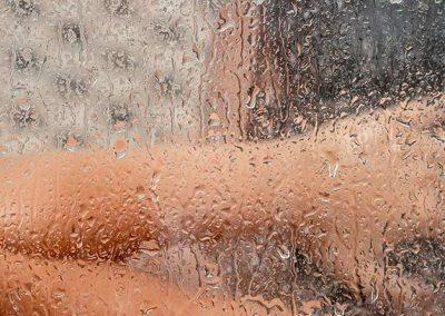 Niña detrás de una mampara de ducha