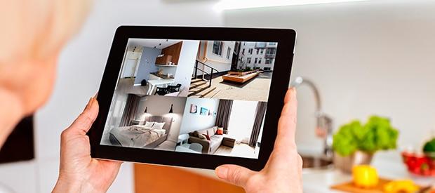mujer de pelo gris controlando sus habitaciones desde una tablet