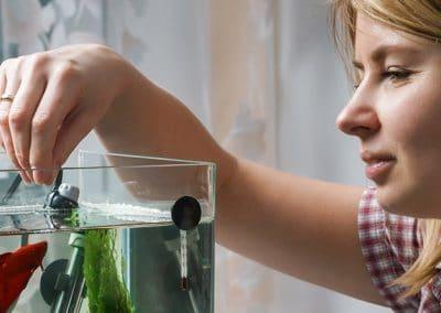 Mujer rubia limpiando el filtro de un acuario.