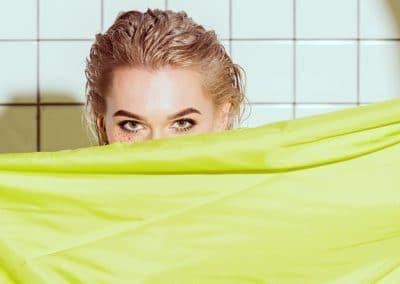 Mujer asomando detrás de una cortina de baño amarilla