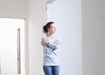 Mujer apoyada en la pared de un pasillo estrecho
