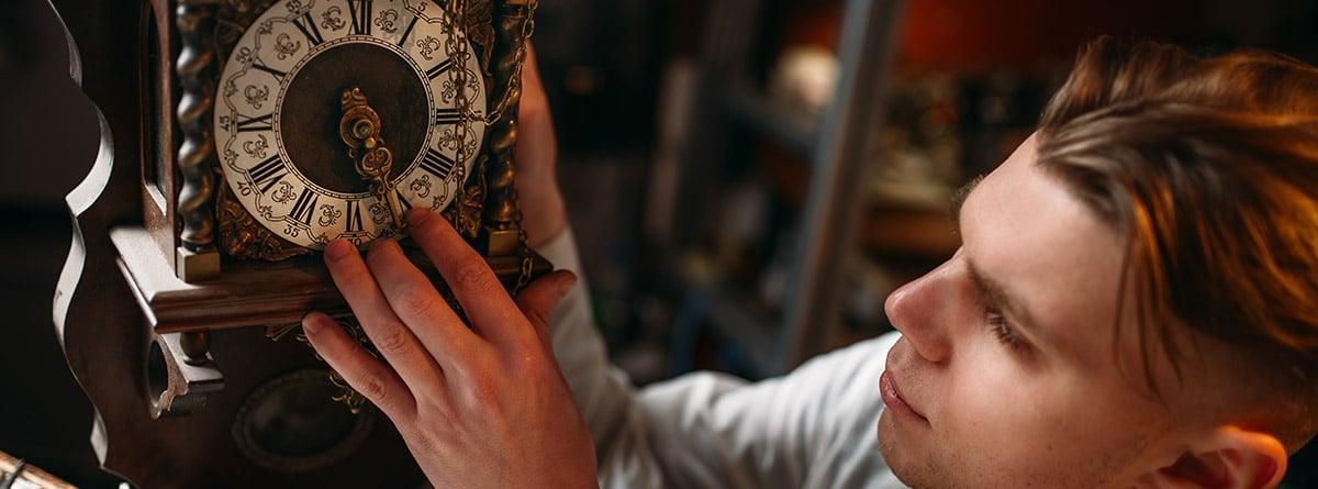 Hombre con bata blanca reparando un reloj de pared
