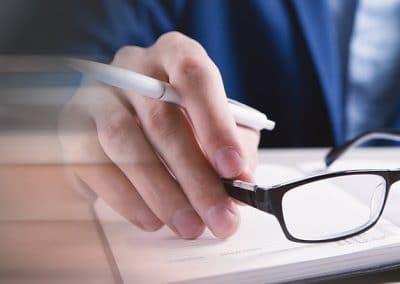 Hombre con gafas en la mano delante de un cuaderno y la maqueta de una casa