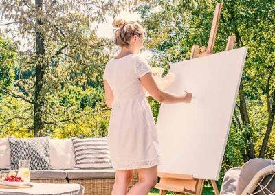 Mujer pintando un cuadro en un patio al aire libre