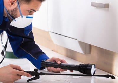 Hombre con traje especial y mascarilla pulverizando un insecticida en el interior de una vivienda