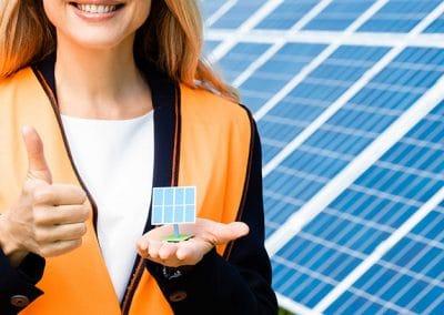 Mujer con chaleco naranja delante de unas placas solares