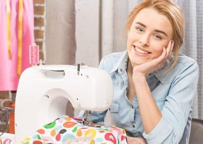 Mujer con máquina de coser y retales de tela
