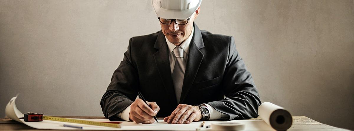 Arquitecto con casco de obra firmando documentos