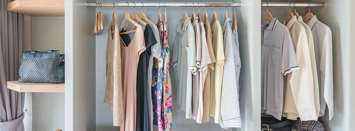 Vista interior de un armario con la ropa colgada en perchas y altillo con cajas