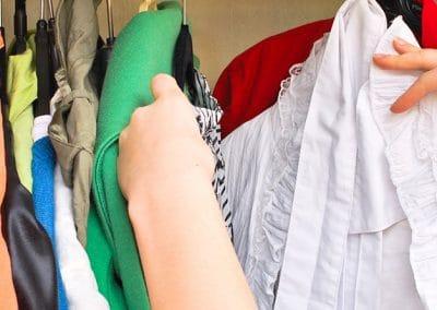 manos en un armario lleno de ropa colgada en perchas