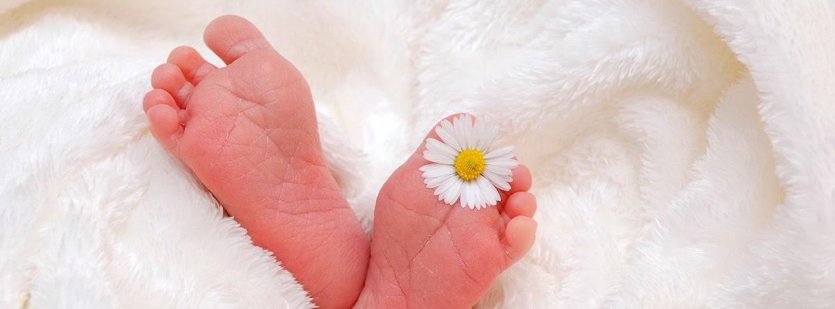 Pies de bebé asomando en una manta blanca