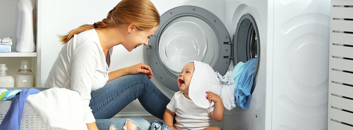 Mujer y niño junto a una lavadora para lavar la ropa del bebé