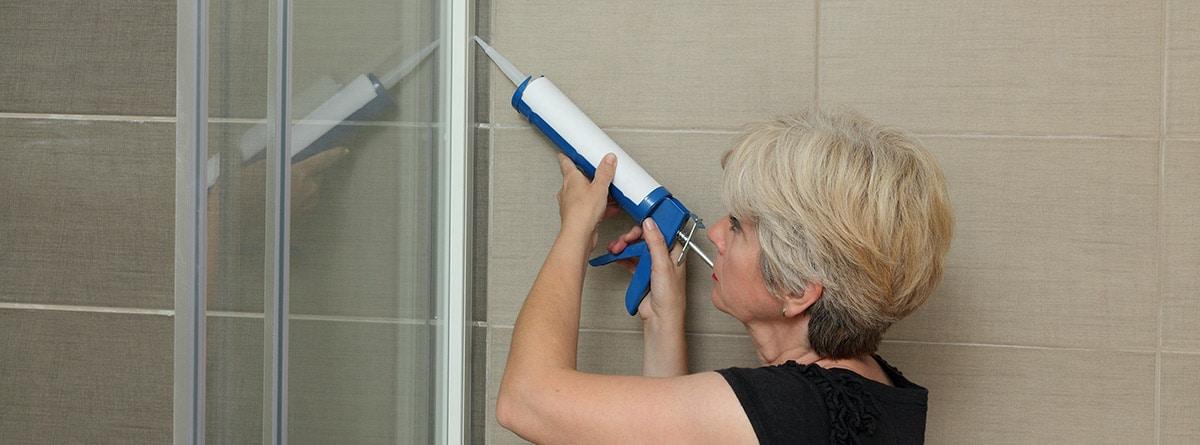 Mujer aplicando silicona en la ducha
