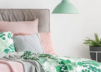 Cama decorada con cojines y sábanas