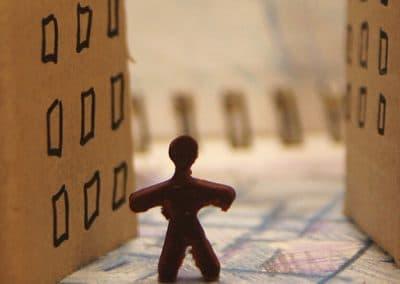 Figura humana y bloques de pisos hechos con cartón