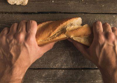 Manos partiendo una barra de pan
