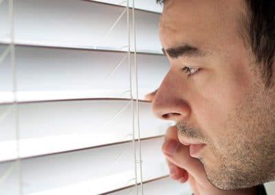 hombre mirando por la persiana de una ventana