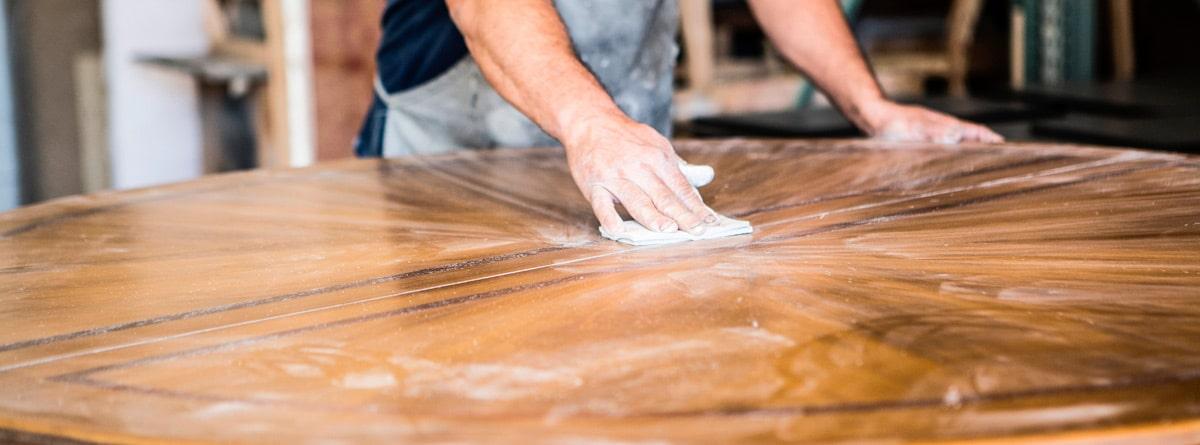 Hombre lijando una mesa para quitar los hongos de la madera