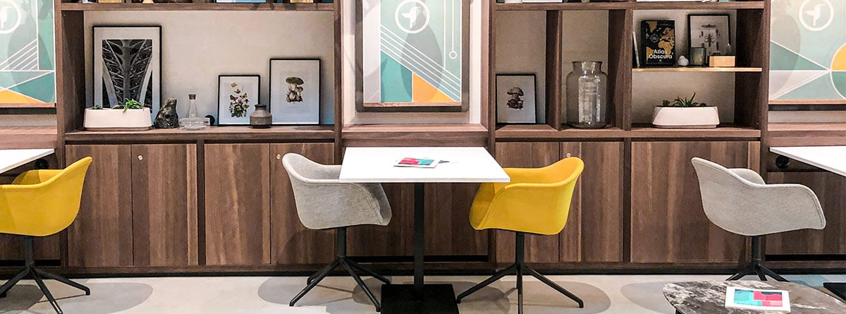 estancia con varios juegos de mesa de comedor y sillas rectangulares amarillas y grises con mueble de madera y cuadros a juego