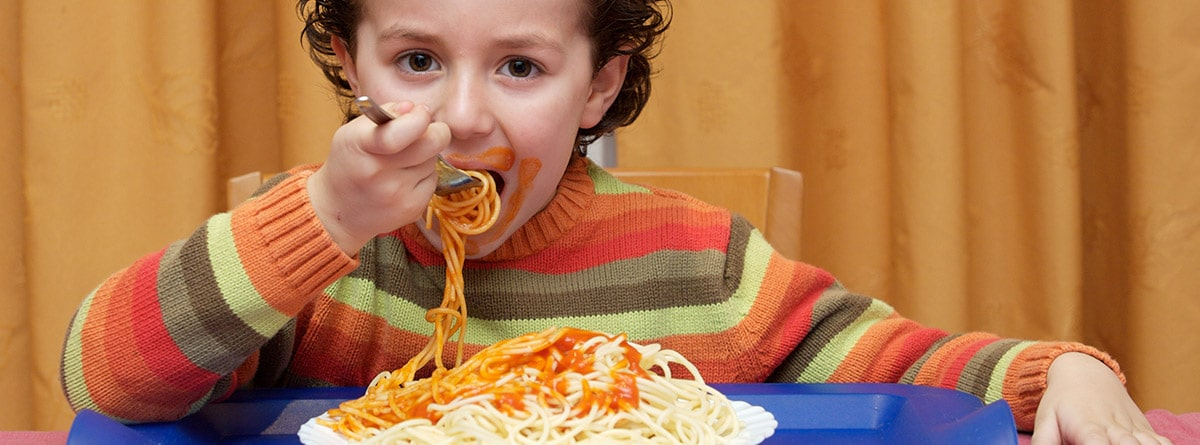 Niño comiendo espaguetis con tomate