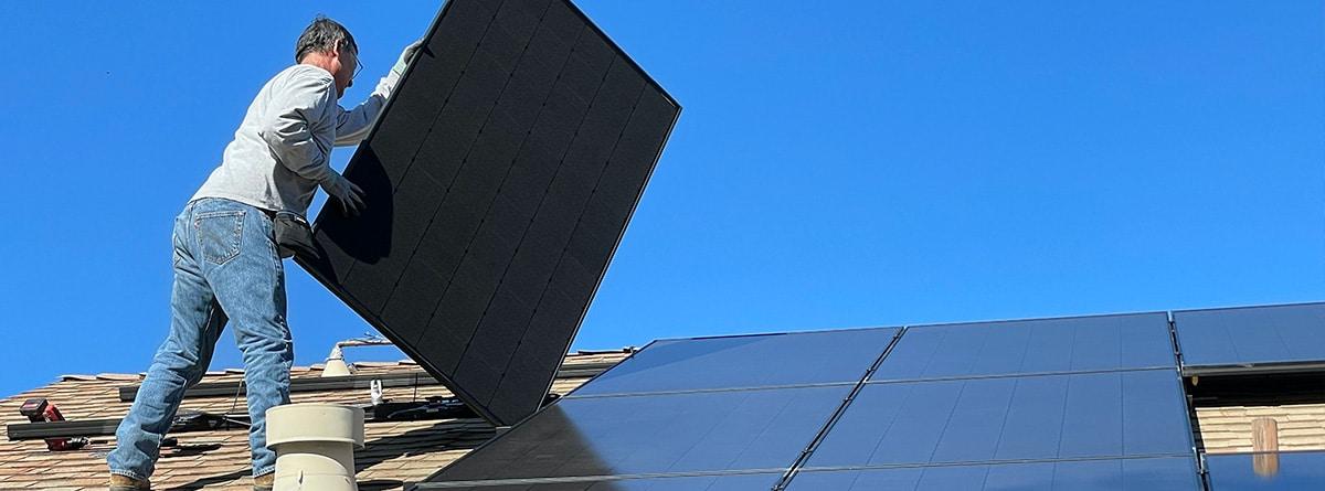 Hombre colocando panel solar en el tejado de su casa