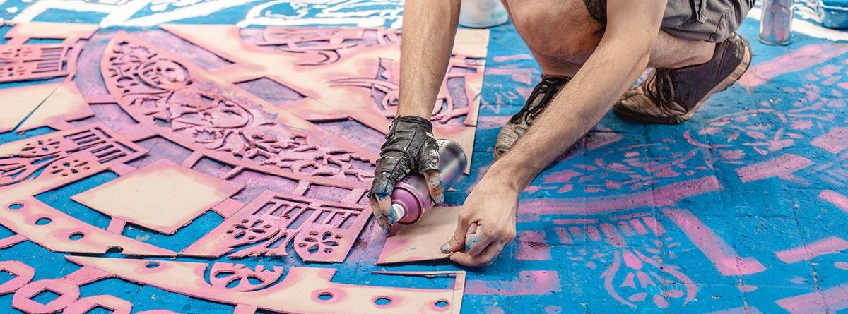 hombre pintando una superficie usando la técnica esténcil con plantillas