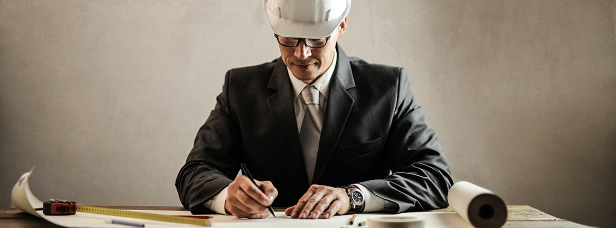 Arquitecto en traje firmando papeles