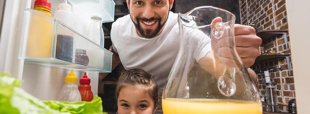 A qué temperatura tener la nevera Alt: Hombre y niña sonriente sosteniendo una jarra de zumo